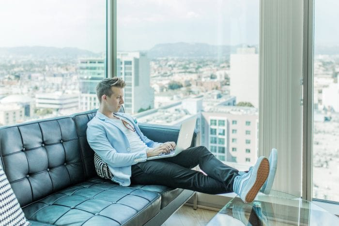 Man sitting on couch by window