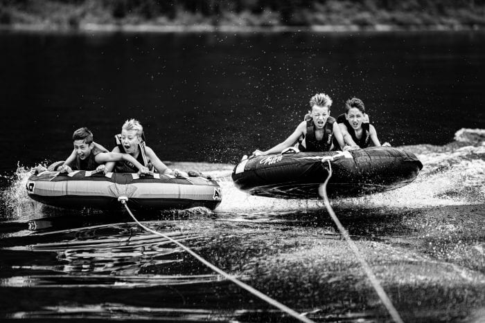 Children water tubing on a lake